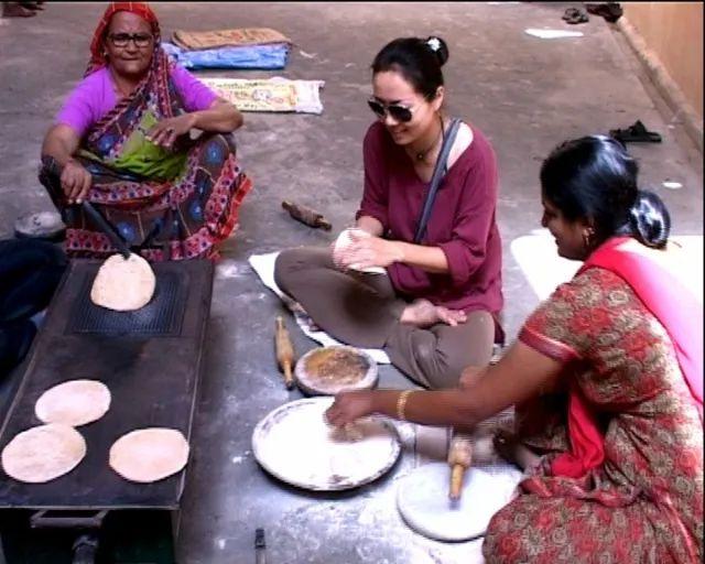 ▲大壶节上,义务为巴巴和信众做饭的印度妇女,吕炜克(中)也参与其中。梁子 摄