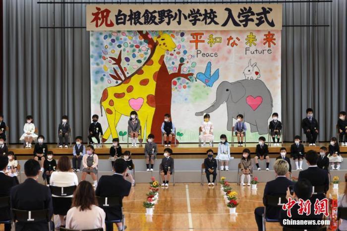 原料图:5月24日,日本山梨县一所幼学举走重生入学仪式,重生们戴着口罩参添开学典礼。