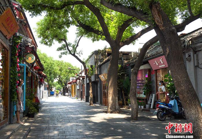 6月18日,南锣鼓巷两家商铺的店员在各自门口隔路聊天。中新网记者 李霈韵 摄