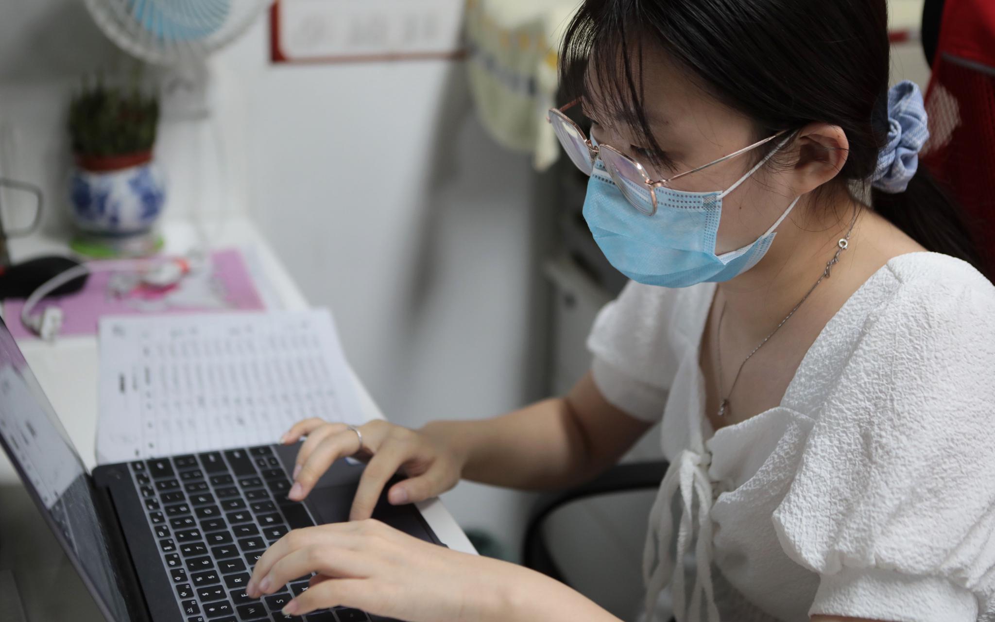 缪雨曈在社区帮忙录入核酸检测信息。摄影/新京报记者 王嘉宁