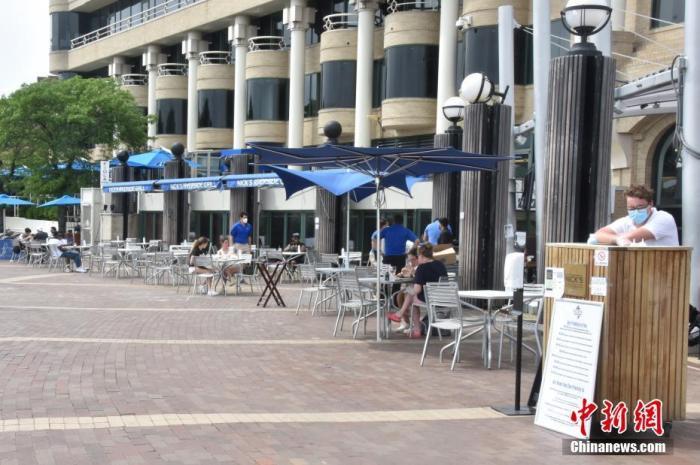 """当地时间5月29日,美国首都华盛顿正式""""解封""""。图为民众在餐厅室外座位保持""""社交距离""""用餐。 中新社记者 沙晗汀 摄"""