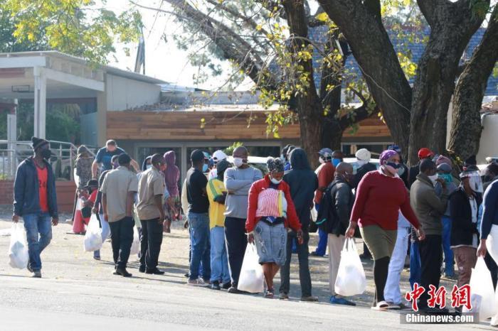进入六月以来,南非新冠肺炎疫情呈现快速增长态势。图为在南非约翰内斯堡一社会救济站,领取救济食品的民众排成长龙。 中新社记者 王曦 摄