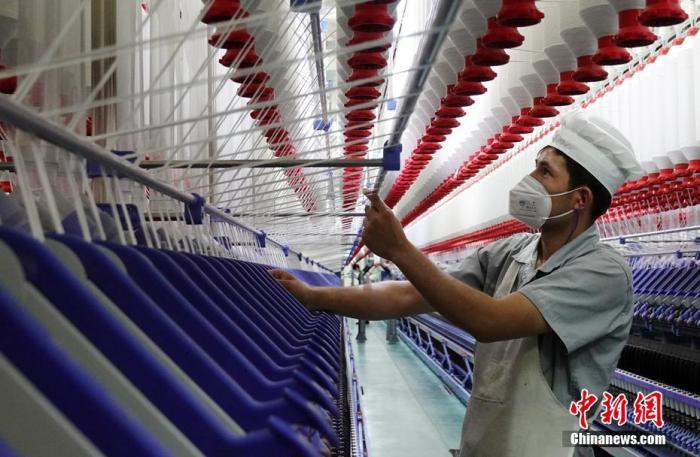 原料图:纺织企业员工正进走生产工序作业。 确·胡热 摄