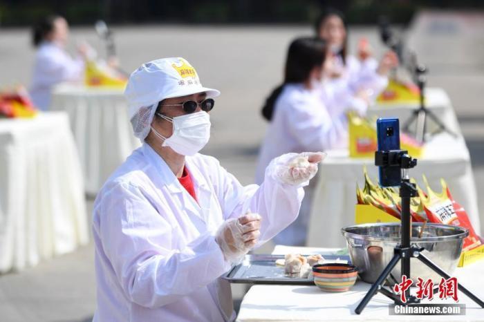 """资料图:一位工人直播包""""辣条馅""""的饺子。中新社记者 杨华峰 摄"""