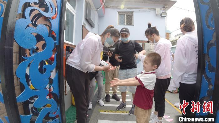 从6月8日起,北京市具备开园条件的北京市幼儿园陆续开园。图为老师检查幼儿手、口等部位。 张兴龙 摄