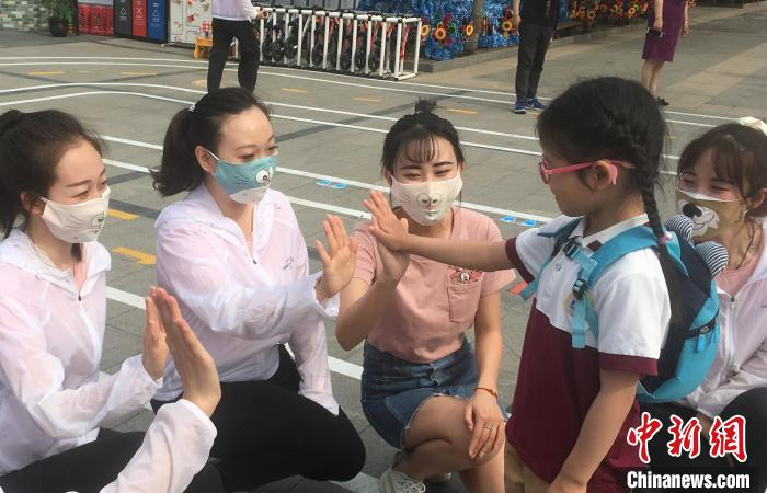 从6月8日起,北京市具备开园条件的北京市幼儿园陆续开园。图为幼儿和老师击掌庆祝返园。 张兴龙 摄