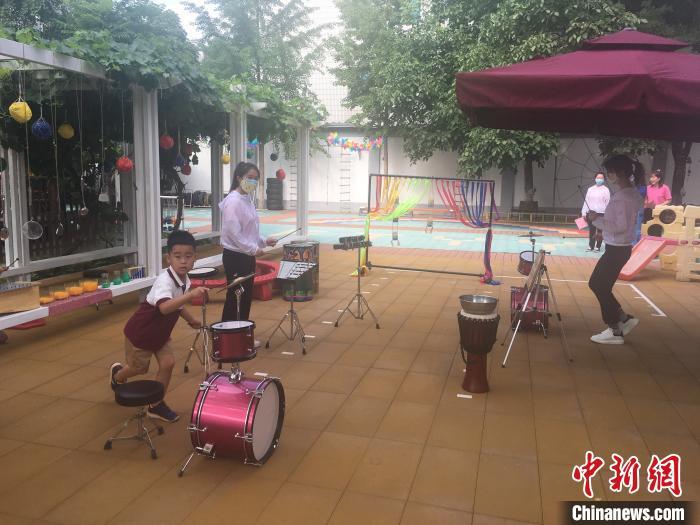 从6月8日起,北京市具备开园条件的北京市幼儿园陆续开园。图为幼儿在园中敲打乐器。 张兴龙 摄