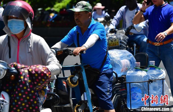 图为福州烈日下骑车忙着送水的工人。 张斌 摄