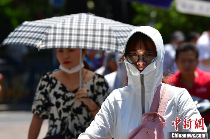 图为福州市民在烈日下出走。 张斌 摄
