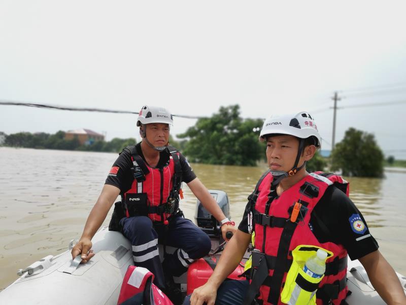 声援队在洪灾现场乘坐冲锋舟搜寻被困者。