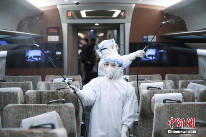 资料图:工作人员在一辆高铁车厢内执行消毒任务。中新社记者 贾天勇 摄