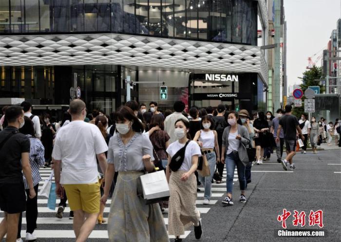 """当地时间6月6日,日本东京都发布新冠肺热疫情""""东京警报""""后的始个周末,当地选择出门逛街的民多数目并异国大幅缩短。图为当地民多佩戴口罩走过东京街头。 中新社记者 吕少威 摄"""