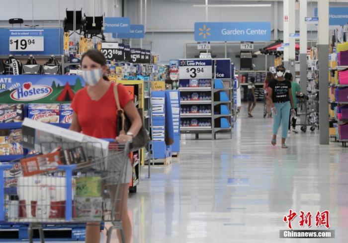 当地时间7月16日,美国得克萨斯州休斯顿地区的一家沃尔玛超市内,顾客们戴口罩购物。日前,美国多家零售商宣布,要求顾客进店时必须戴口罩等面部遮挡物。中新社记者 曾静宁 摄