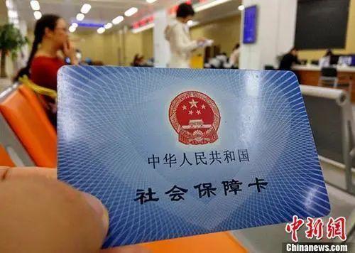 资料图:某市民服务中心前来办理社保业务的民众展示自己的社会保障卡。中新社记者 张斌 摄