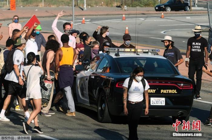 资料图:当地时间5月27日,美国洛杉矶市中心,抗议者围住了一辆巡逻的警车。