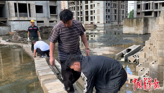 业主们在积水严重的空地上铺起小路。