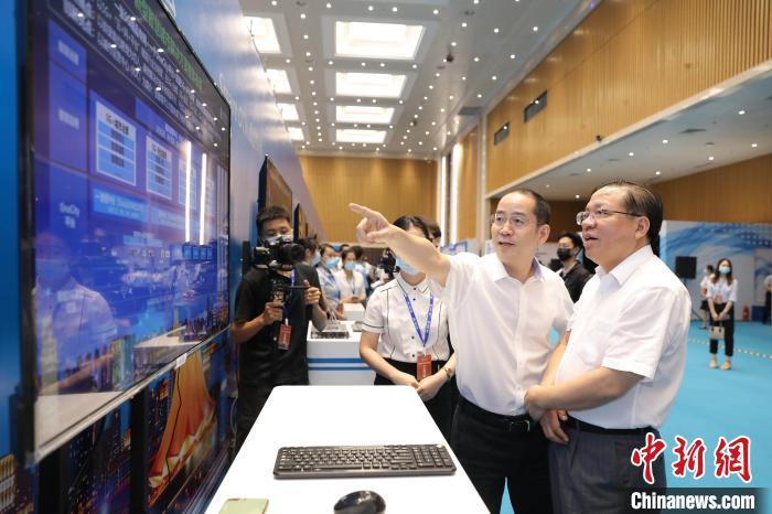 广西壮族自治区党委常委、自治区常务副主席秦如培(右)了解5G+智慧城市建设进展。 文泉 摄