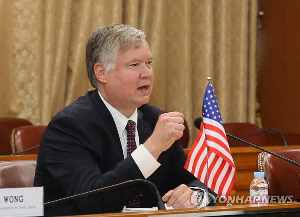比根在同李度勋说话 图片来源:韩联社