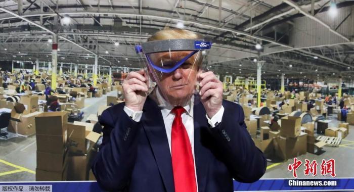 原料图:图为美国总统特朗普手举防护面具。
