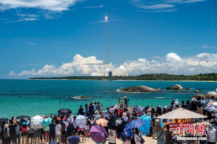 图为民众在海边观看长征五号遥四火箭发射升空。 骆云飞 摄