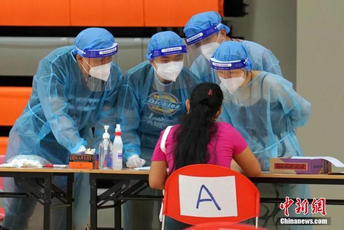 资料图:8月25日上午,有外佣陆续来到设于香港港湾道体育馆的临时样本采集中心,接受新冠病毒检测服务。 中新社记者 张炜 摄