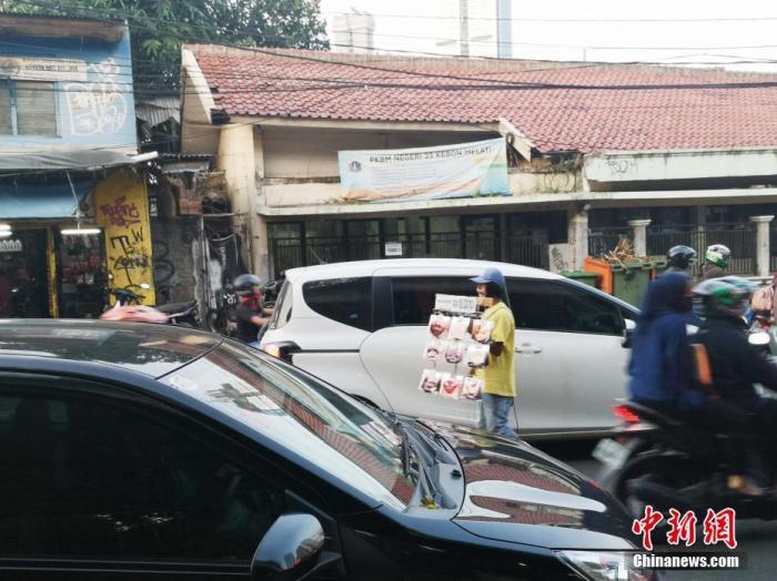一名小贩在车流中穿梭卖口罩。</div><bdo lang=