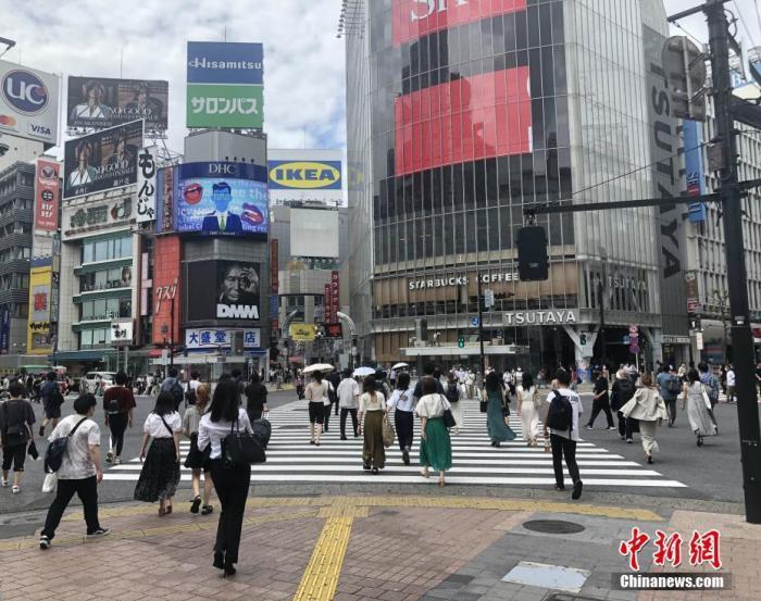 资料图:日本民众穿过涩谷车站前的交叉路口。 中新社记者 吕少威 摄
