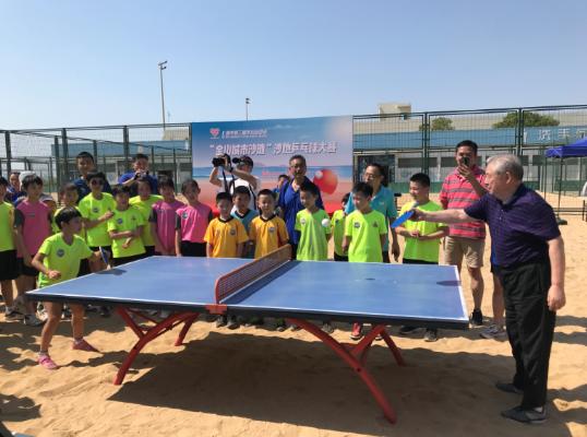 图说:国际乒联终身名誉主席徐寅生(右)与参赛小选手为比赛开球 陈一平 摄