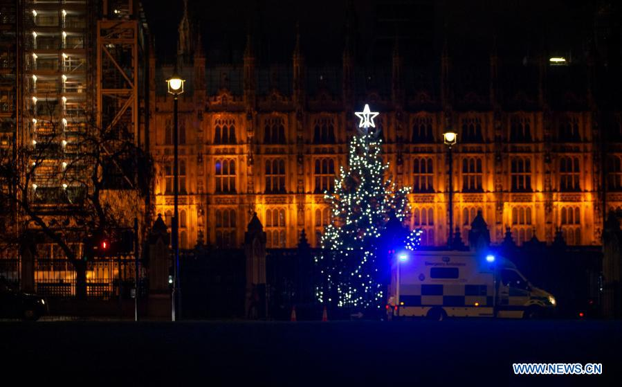 An ambulance passes by the Christmas tree outside the Houses of Parliament in London, Britain, on Dec. 23, 2020. (Xinhua/Han Yan)