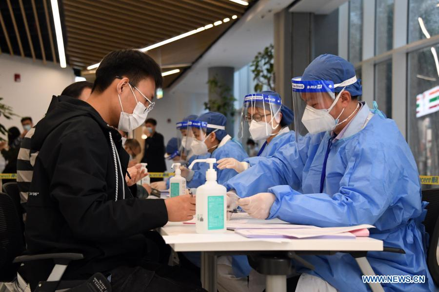 A staff member (front, L) signs a letter of informed consent at a temporary COVID-19 vaccination site at a company in the ZPark Phase 2 in Haidian District of Beijing, capital of China, Feb. 22, 2021. It is expected to take two days to complete the vaccination of more than 3,800 employees of the enterprise. (Xinhua/Ren Chao)
