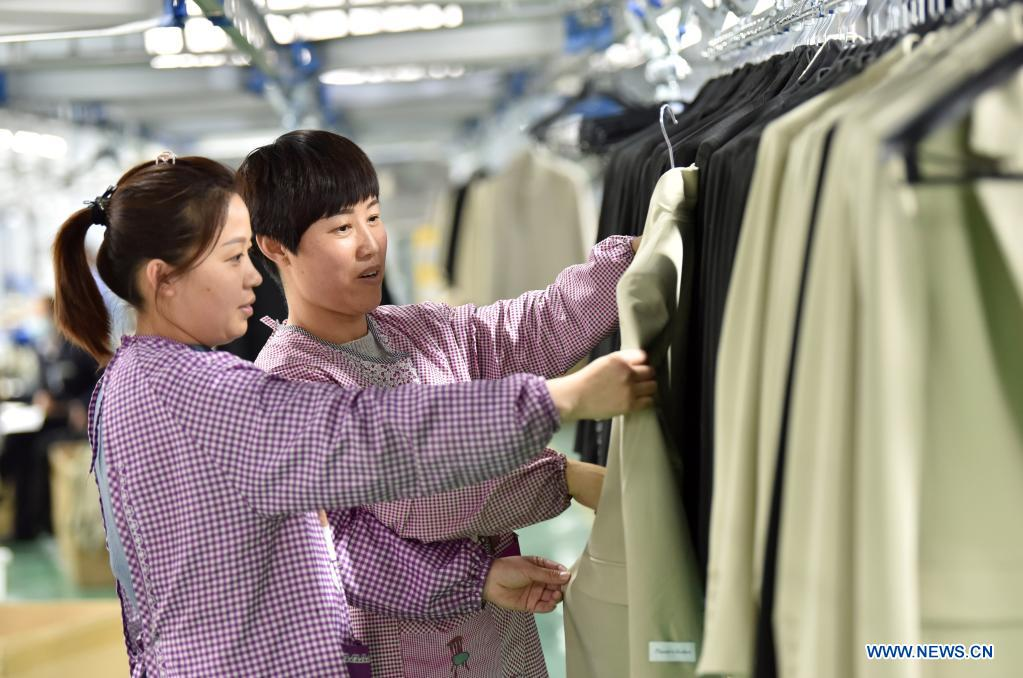 Employees work in a garment factory in Nanhe District of Xingtai City, north China's Hebei Province, March 28, 2021. The local government has been taking measures to build up a variety of platforms in an effort to provide job opportunities for local villagers. (Xinhua/Zhu Xudong)