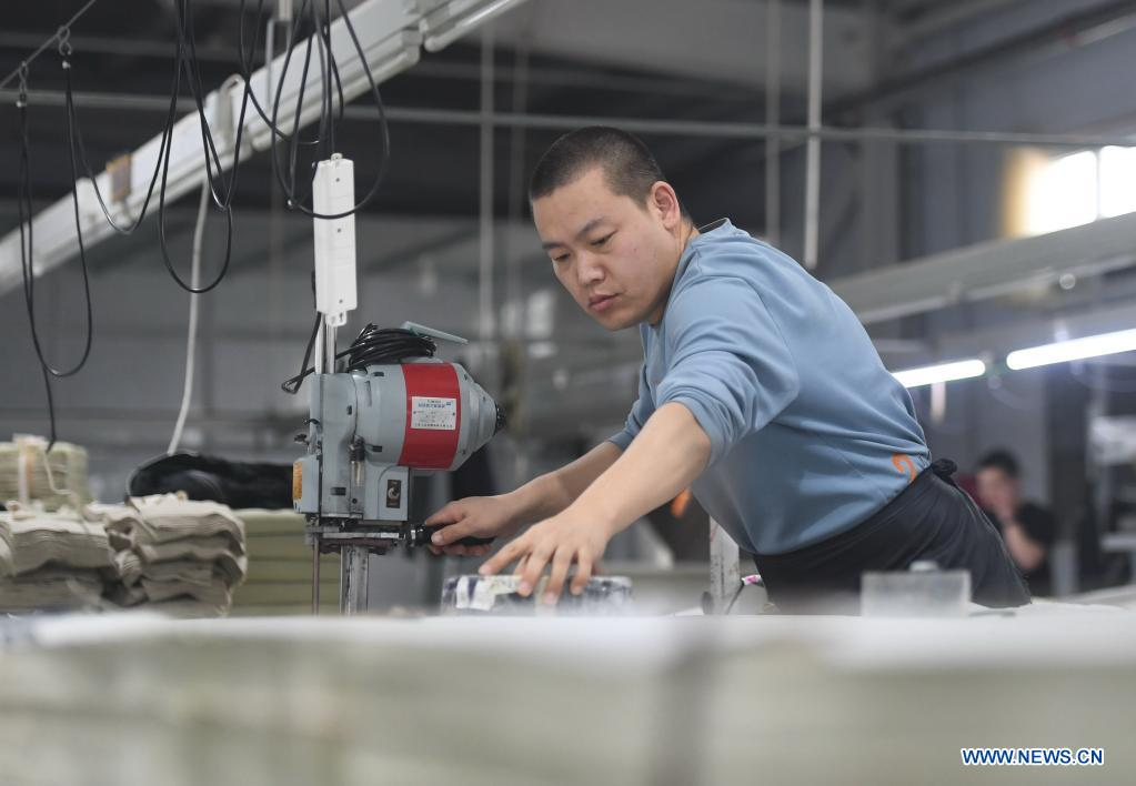 An employee works in a garment factory in Nanhe District of Xingtai City, north China's Hebei Province, March 28, 2021. The local government has been taking measures to build up a variety of platforms in an effort to provide job opportunities for local villagers. (Xinhua/Zhu Xudong)