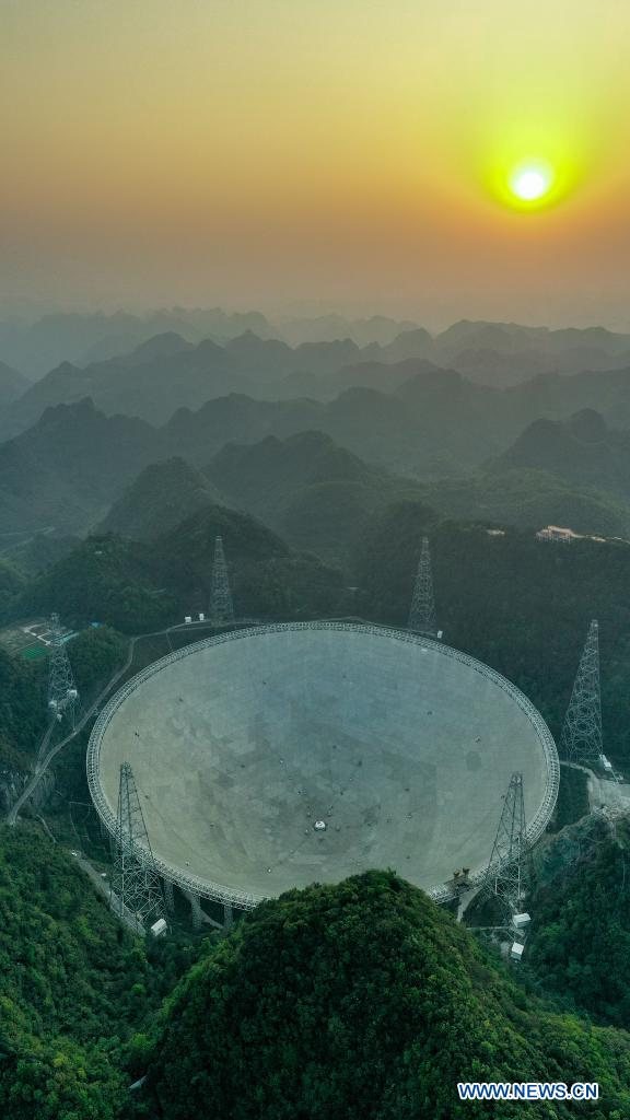 Aerial photo taken on March 29, 2021 shows China's Five-hundred-meter Aperture Spherical Radio Telescope (FAST) under maintenance at sunset in southwest China's Guizhou Province. China's FAST officially opened to the world starting Wednesday. (Xinhua/Ou Dongqu)