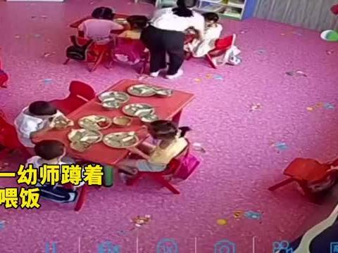 一幼师蹲着给小朋友喂饭,一男孩默默为老师搬凳子