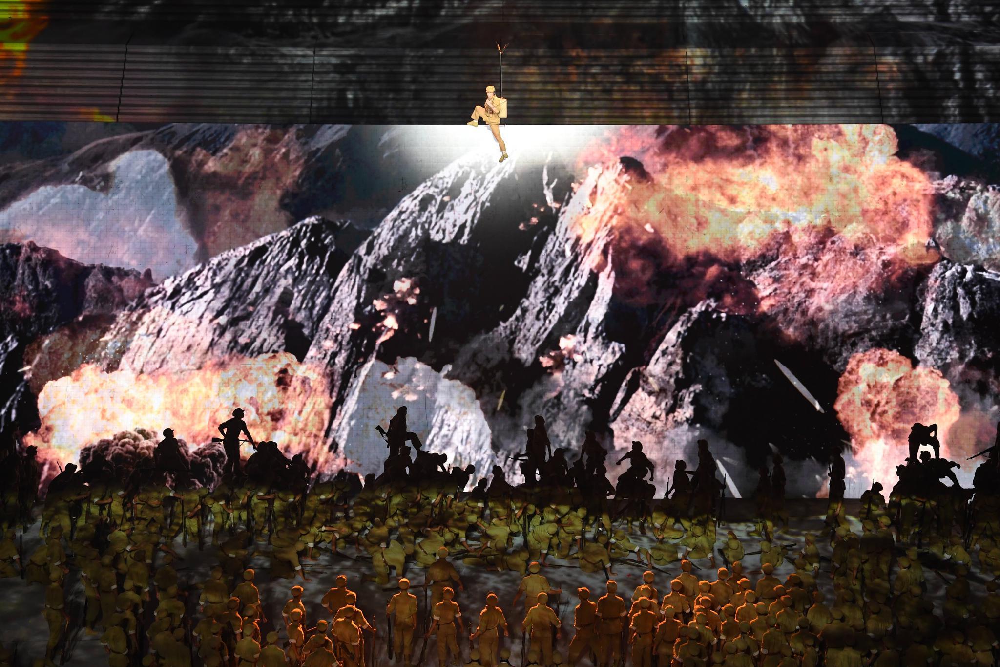 情景合唱与舞蹈节目《战旗美如画》中,舞台地面中央长30米、宽9米的翻屏缓缓升起