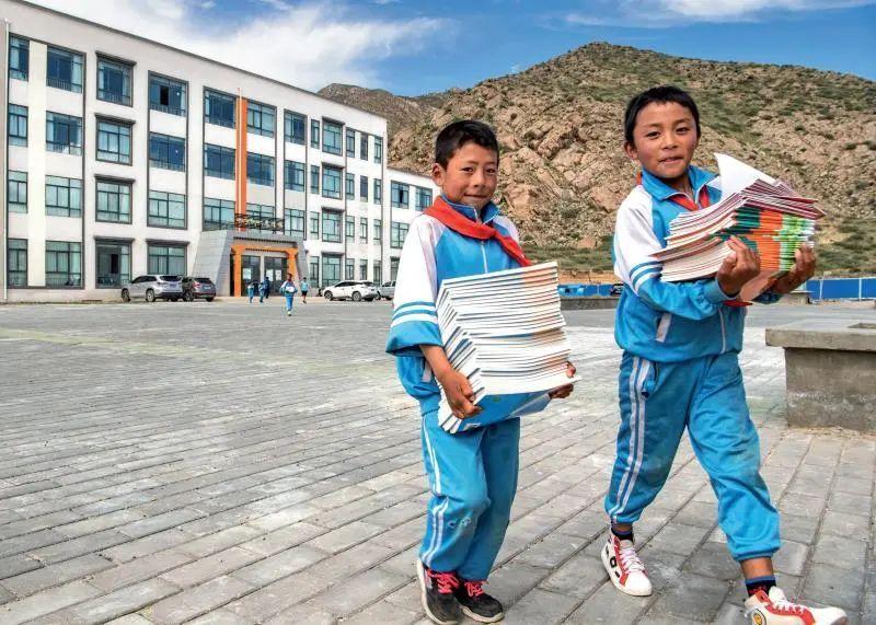 ▲西藏山南市贡嘎县森布日幸福家园九年一贯制学校的学生们在搬新书( 2020年8月24日摄) 孙非摄 / 本刊