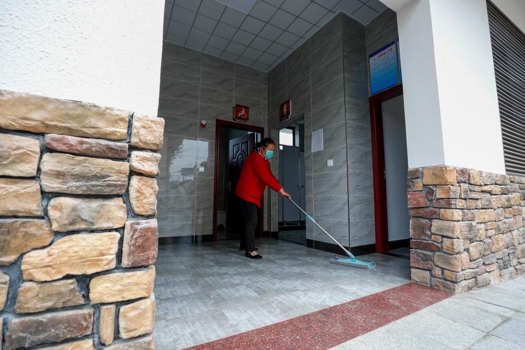 2020年4月8日,重庆市沙坪坝区中梁镇龙泉村村民吴桂慧在打扫村里的公厕。 新华社发(黄伟 摄)