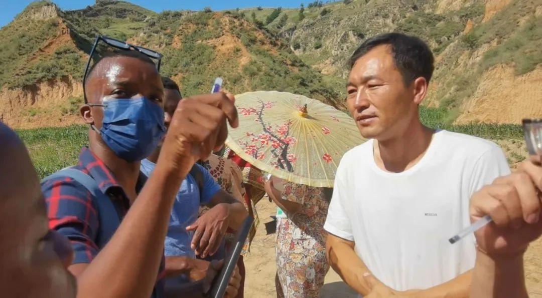 7月14日,山西省吕梁市兴县蔡家崖乡沙壕村,喀麦隆留学生门杜向村民请教脱贫经验。