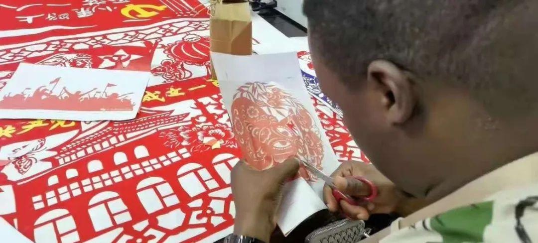 7月14日,山西省吕梁市兴县蔡家崖乡沙壕村,非洲青年在兴县体验非遗剪纸艺术。