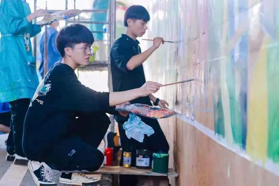 云南大学艺术与设计学院团队为云南省万溪冲村入口绘制墙绘。云南大学供图