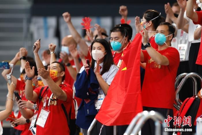 当地时间7月25日,郭晶晶(中)为施廷懋、王涵助威。当日,东京奥运会跳水女子双人三米板决赛在东京水上运动中心举行,中国组合施廷懋、王涵以326.40分摘得金牌。中新社记者 富田 摄