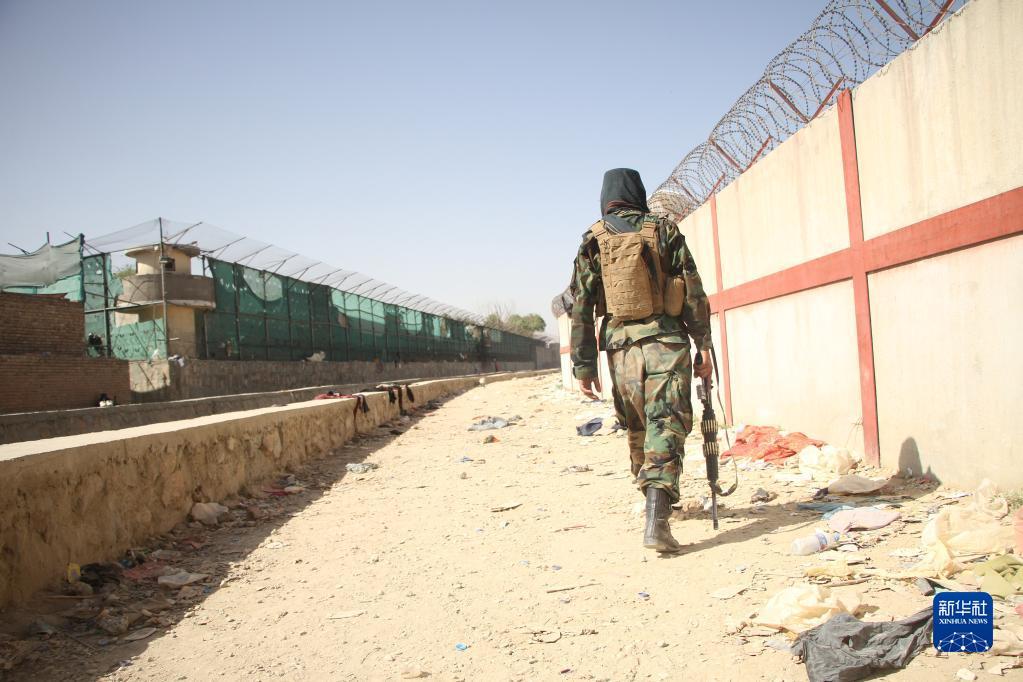 8月27日,一名阿富汗塔利班人员查看喀布尔机场附近的爆炸现场。图自新华社(塞夫拉赫曼・萨菲摄)