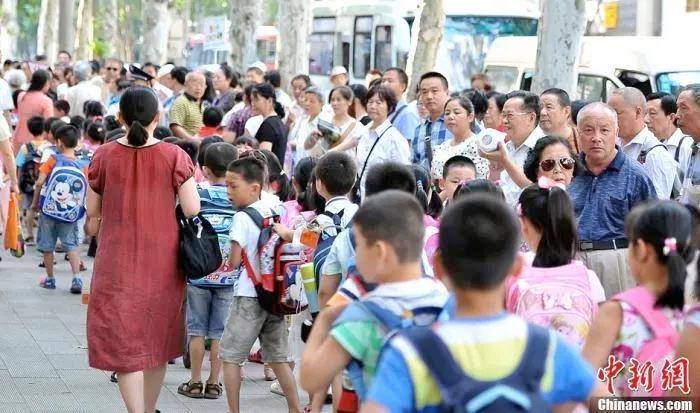 资料图:武汉一小学门外家长接孩子放学。中新社发 张畅 摄