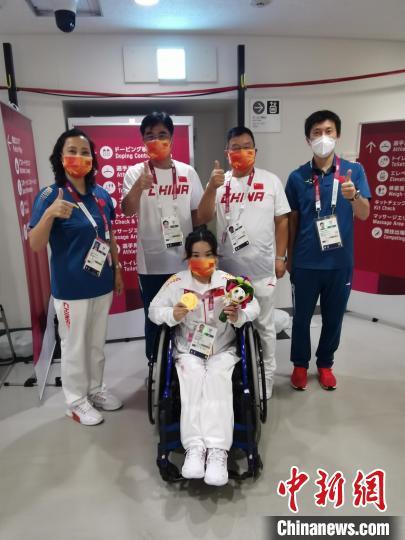 夺冠后的郭玲玲与举重队领队、教练员合影。 中国残联供图