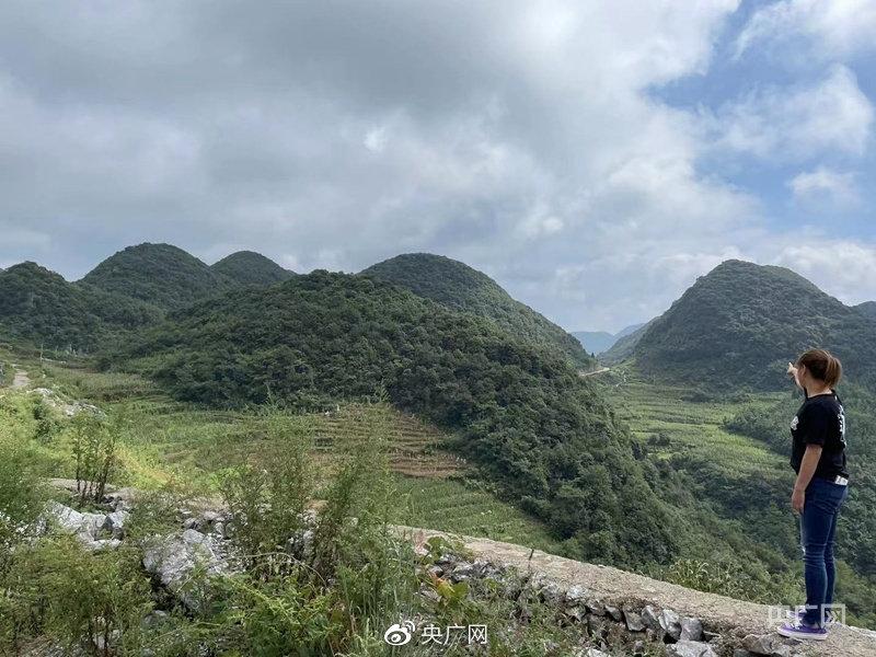 马艺珈伊指向远处山丘,自行车赛道还要再拐几个弯
