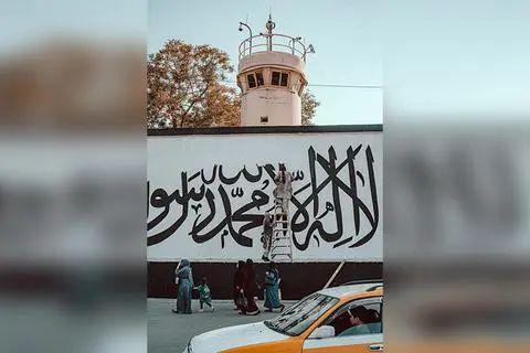 ▲塔利班成员在美使馆墙上画旗,路人扭头观看