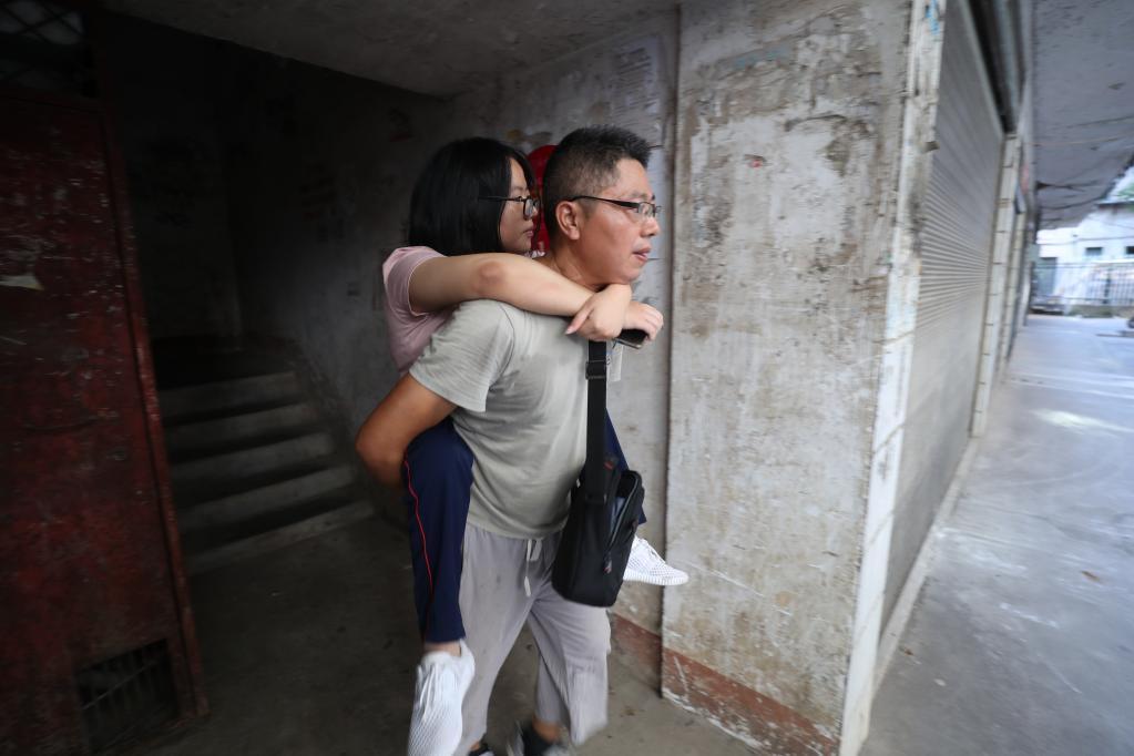 在湖南省衡南县三塘镇,谢培军背着女儿下楼。(曹正平摄)