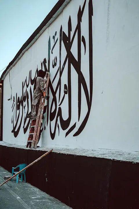 ▲塔利班成员在美使馆墙上画旗
