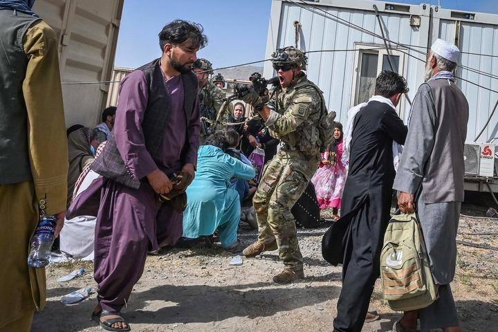 8月16日,在阿富汗喀布尔机场,一名美军士兵用枪指向一名阿富汗男子。新华社/法新