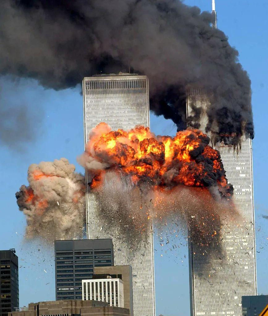 2001年9月11日,美国纽约,被恐怖分子劫持的民航飞机撞击纽约世界贸易中心,浓烟从纽约世贸中心北塔滚滚而出,15分钟后第二架联合航空公司175号航班撞击世贸中心南塔。(图源:视觉中国)